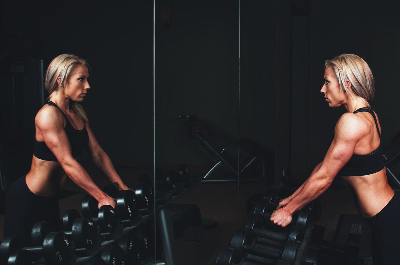 mulher se olhando no espelho na academia