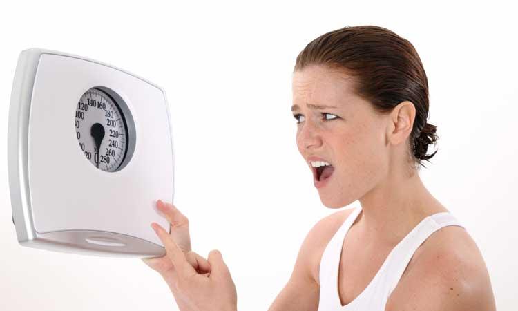 mulher brigando com balança devido ao efeito platô